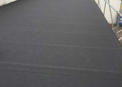 Finishing touches to the pergouet garage in Honiton after re-felting using a charcoal colour, high performance mineral