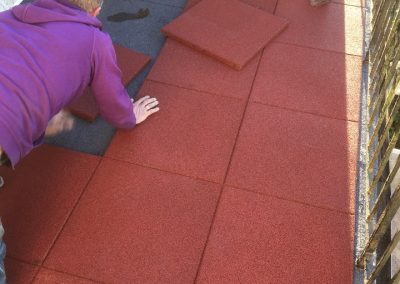 Rubber interlocking promenade tiles being laid on balcony. Firm under foot and ideal for seating table and chairs